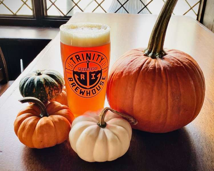 Fall brew from Trinity Brewhouse in a glass on a table with pumpkins.