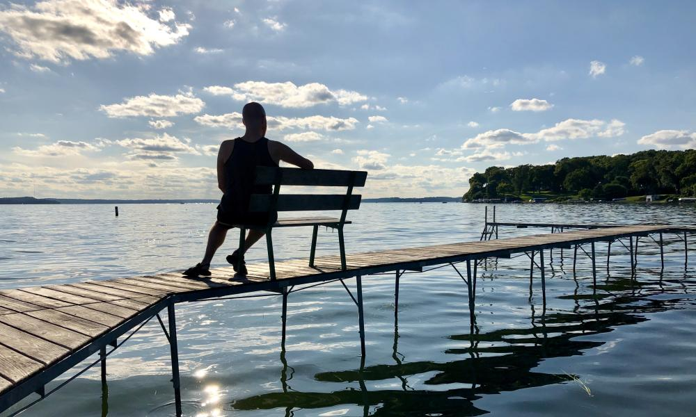 An individual overlooks the lake while sitting on a bench along a pier