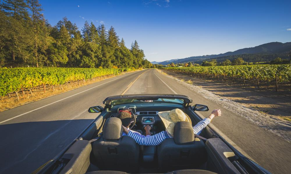 Visitors enjoy the sunshine and fresh air in their convertible on a drive through Napa Valley.