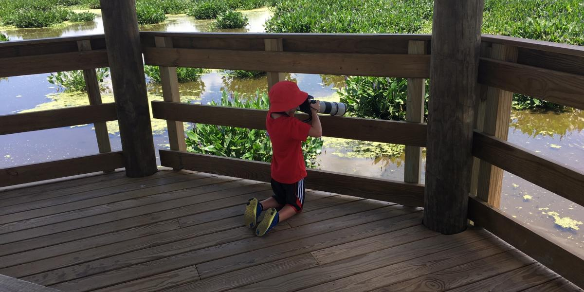 Kid with binoculars at Cattail Marsh in Beaumont, TX