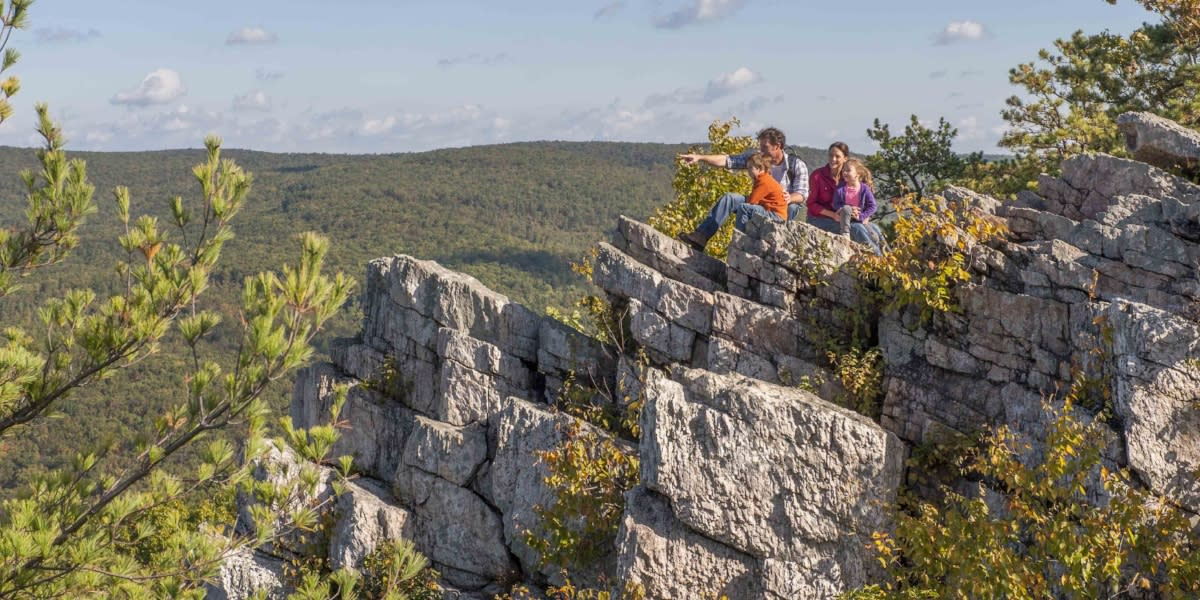 Family sitting on rocks looking at the view on Pole Steeple Trail at Pine Grove Furnace State Park