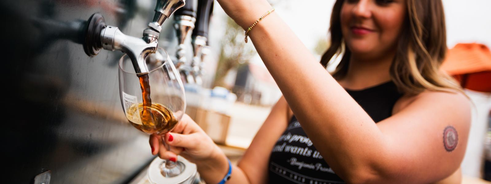 A woman pouring beer from a tap into a glass at SLO Cal bar