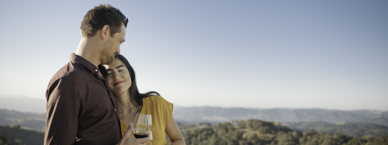 Man and Woman Hugging Outdoors While Drinking Wine