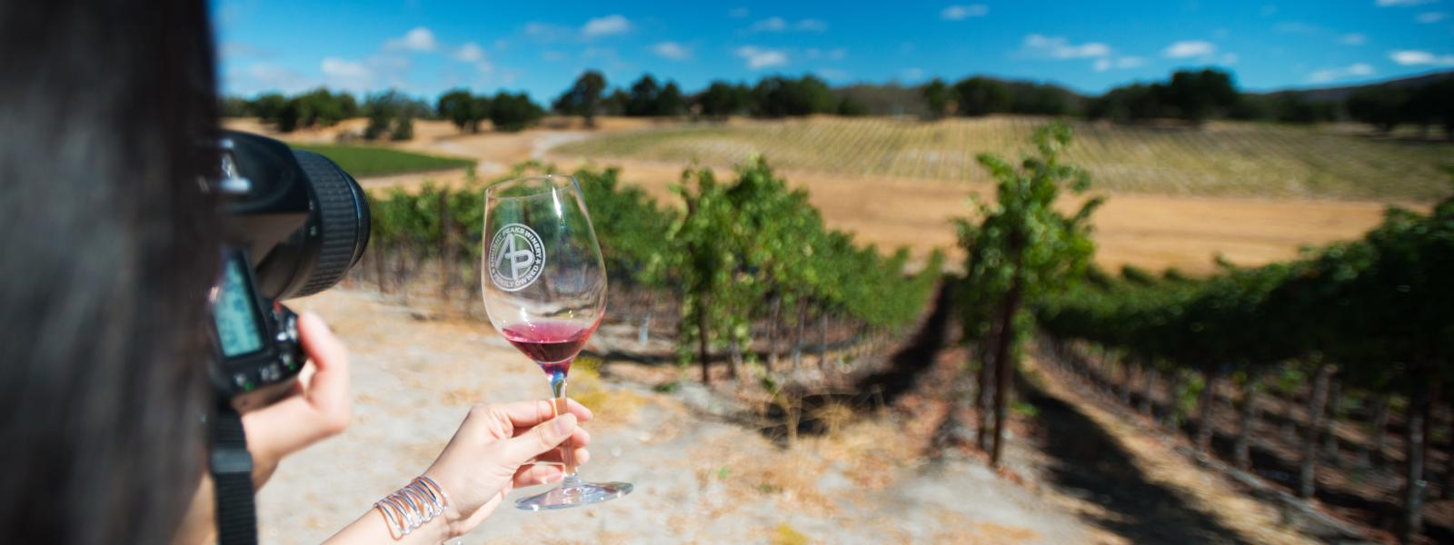 A photographer taking photos of a wine glass overlooking a SLO Cal Vineyard