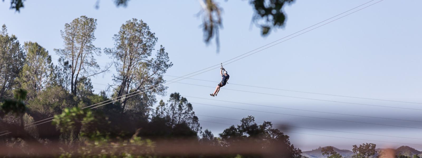 Man zip lining through the trees in San Luis Obispo