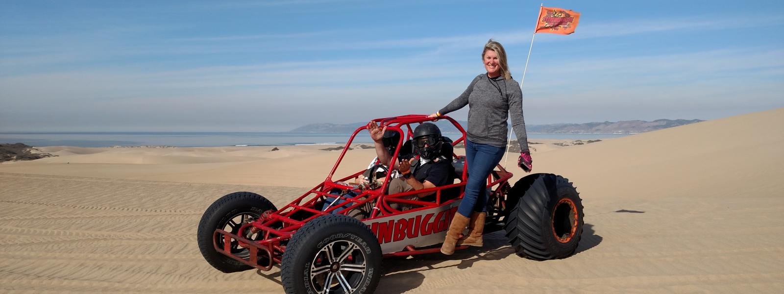 People posing for a picture in a Dune Buggy at the sand dunes in San Luis Obispo