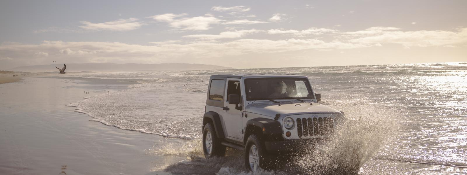 A white Jeep diving on a San Luis Obispo beach, splashing through the water