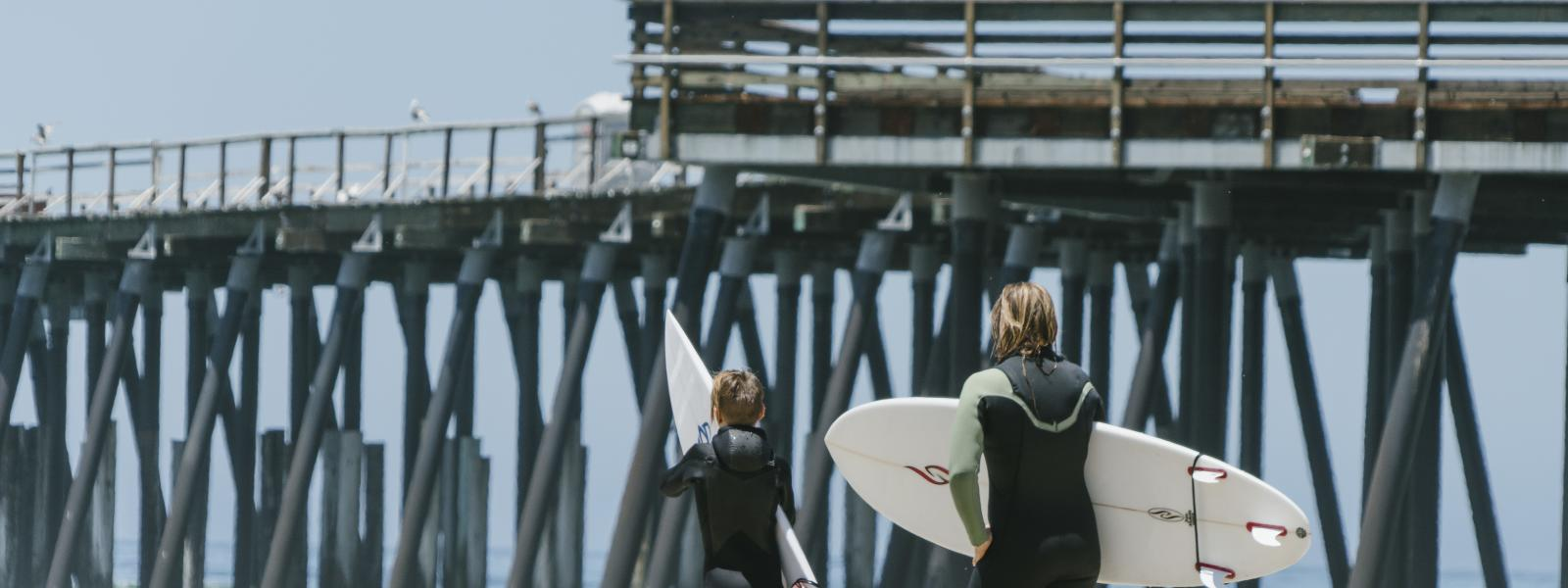 Surfers prepare to enter the water near the Pismo Beach Pier in SLO CAL