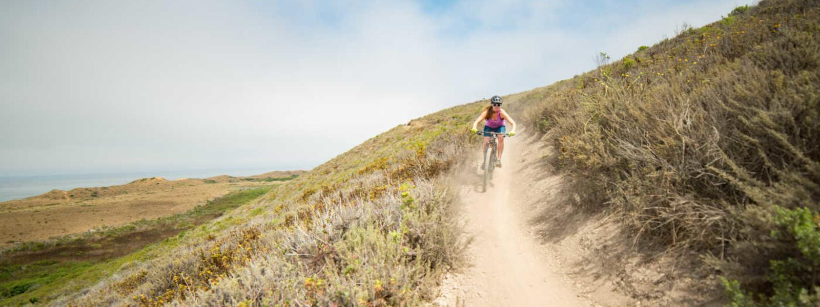 A woman biking down a dirt path in San Luis Obispo