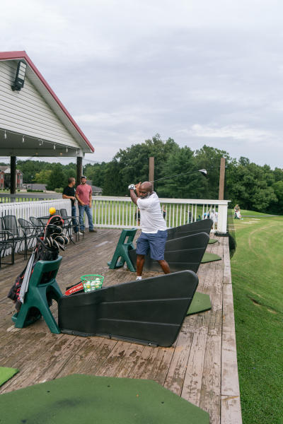 A golfer making a swing on the driving range at Heartland Golf Pub