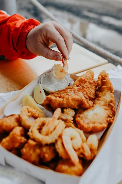 a person eating a fried fish and shrimp basket