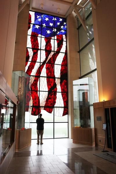 A man admiring the stained glass American flag at the Dole Institute.