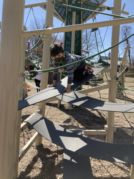 A child climbs a play structure at Kinder Farm.