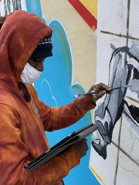 Deonte Ward paints a mural of Carr's Beach.