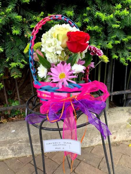 A child's May Day Basket sits on a stool.