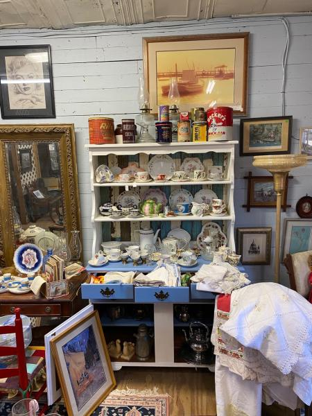 Captain Harvey's shelves packed with vintage finds like tea cups and saucers.