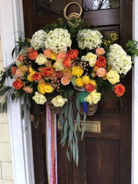 A May Day basket with ribbons hanging down and beautiful hydrangeas, roses and ranunculus