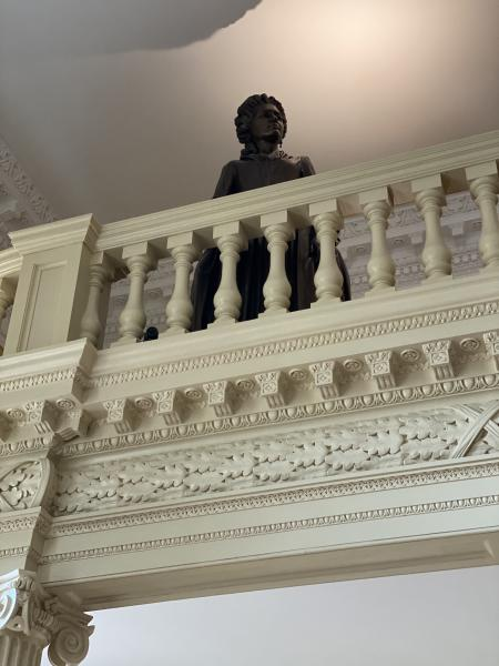 Molly Ridout statue on  the balcony of the State House.