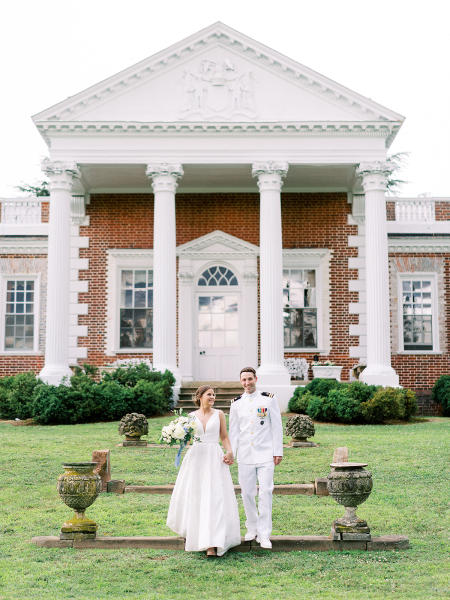Navy groom and bride in front of Whitehall Manor.