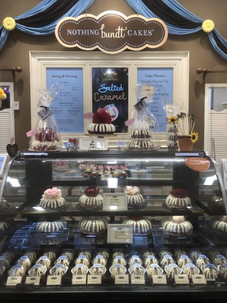 A display case with all size of bundt cakes.