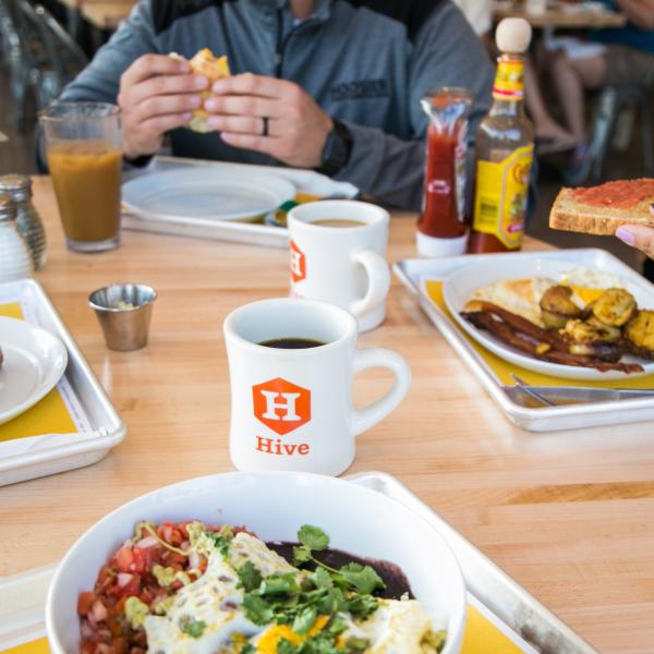 Table of food and Hive coffee cups at Hive Breakfast