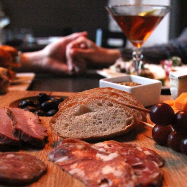 A couple holding hands at a table with a charcuterie board and martini