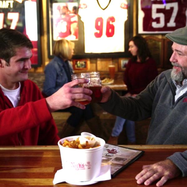 Two men cheers-ing beers with a bowl fries at Nick's English Hut