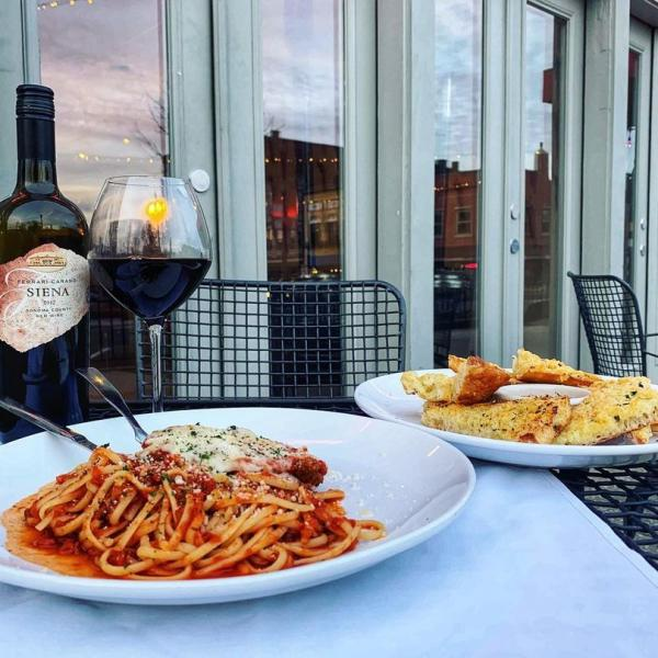 Two dinner plates and a bottle of wine on a patio table at Grazie Italiano In Bloomington, IN