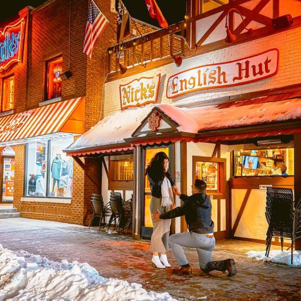 A man proposing to a woman in front of Nick's English Hut