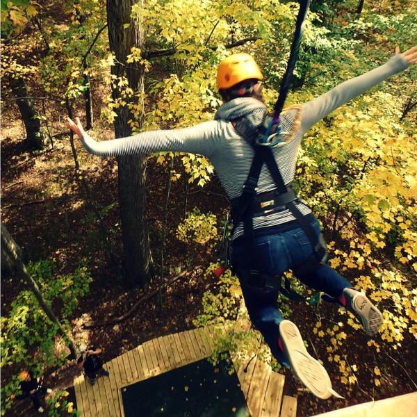 Woman ziplining during fall foliage.