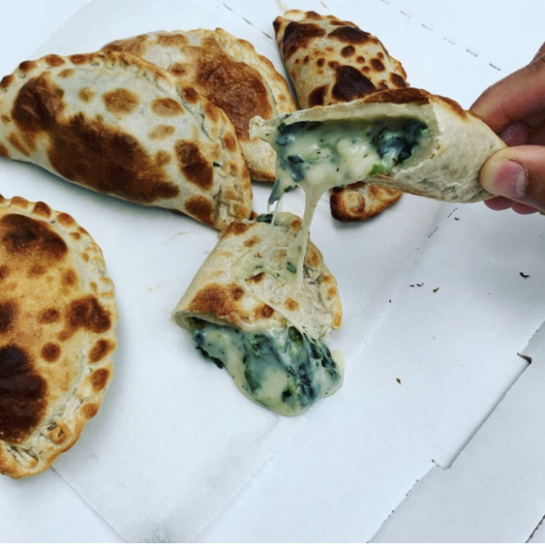 Gooey melted cheese oozed out of a freshly-cooked Empanada from Houston's 5411 Empanadas