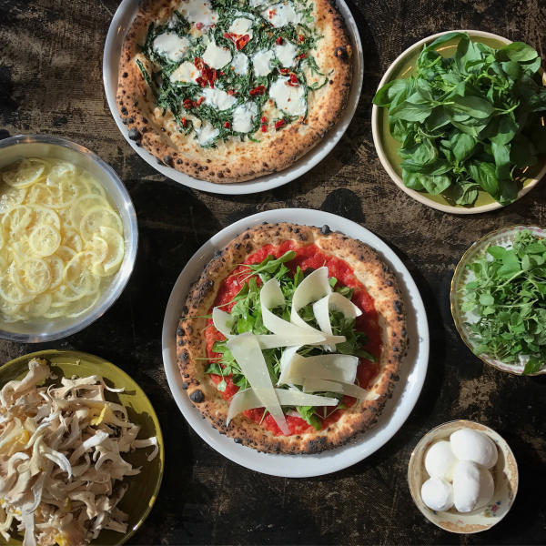 A Dopo Pizza is topped with fresh ingredients and cooked in a wood-fire oven.