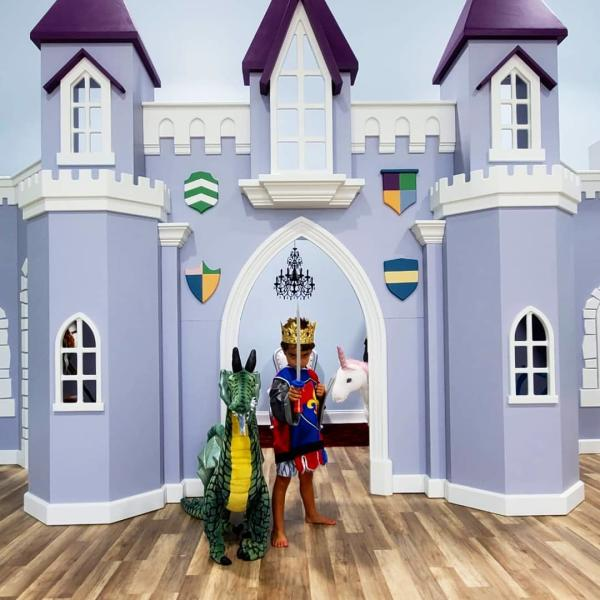 Young boy defending the castle alongside a dragon at Frogs, Snails, and Fairy Tales.