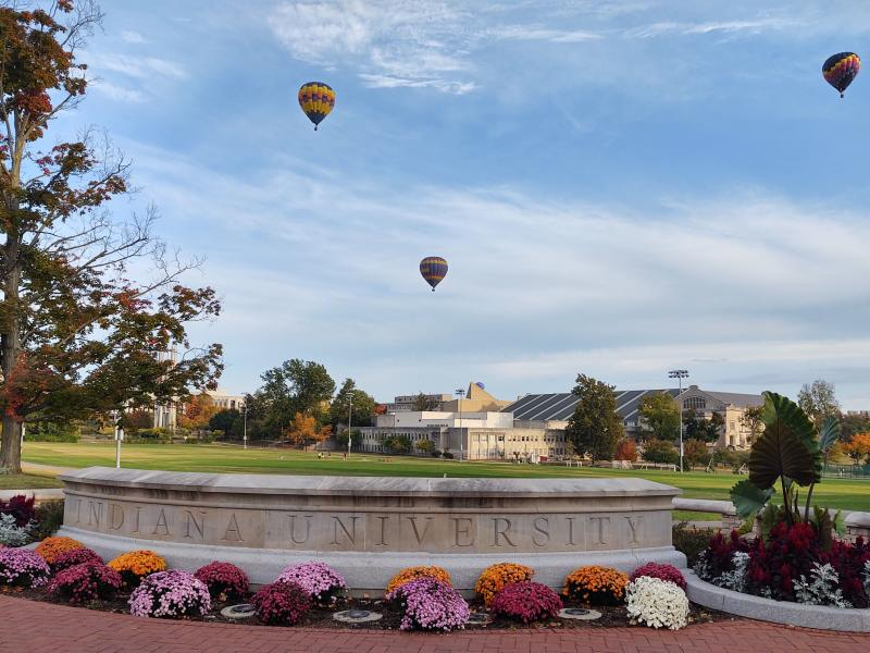 Three hot air balloons floating over IU