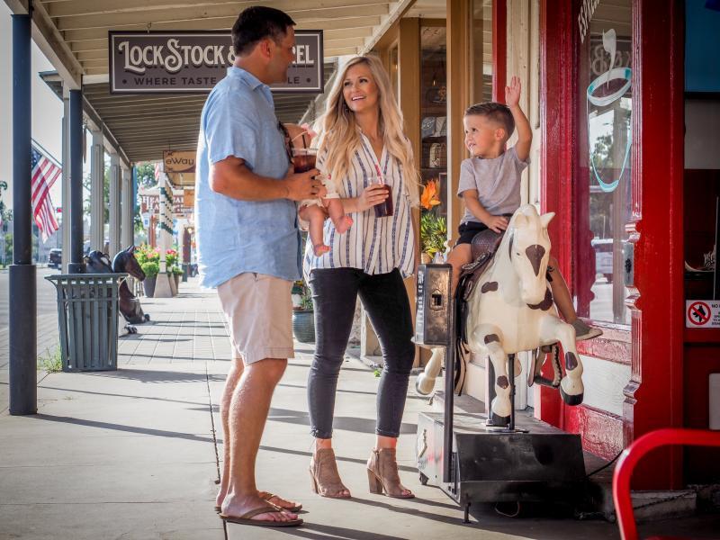 A family on Fredericksburg, TX Main Street, with son riding a horse amusement ride