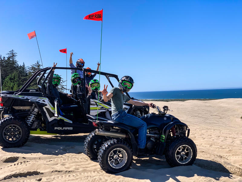 Two off road vehicles full of adventurous people on the Oregon Dunes.