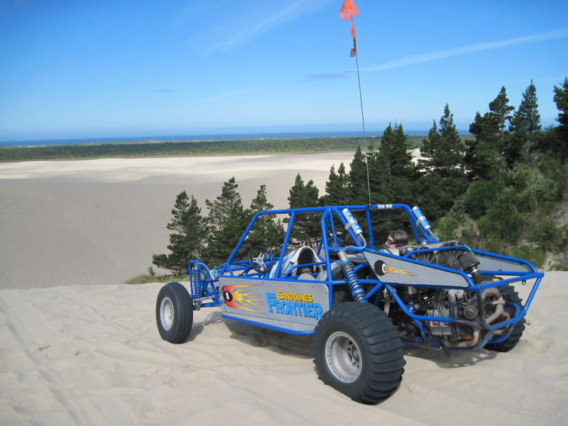 A dune buggy sits atop a large dune looking out towards the sea