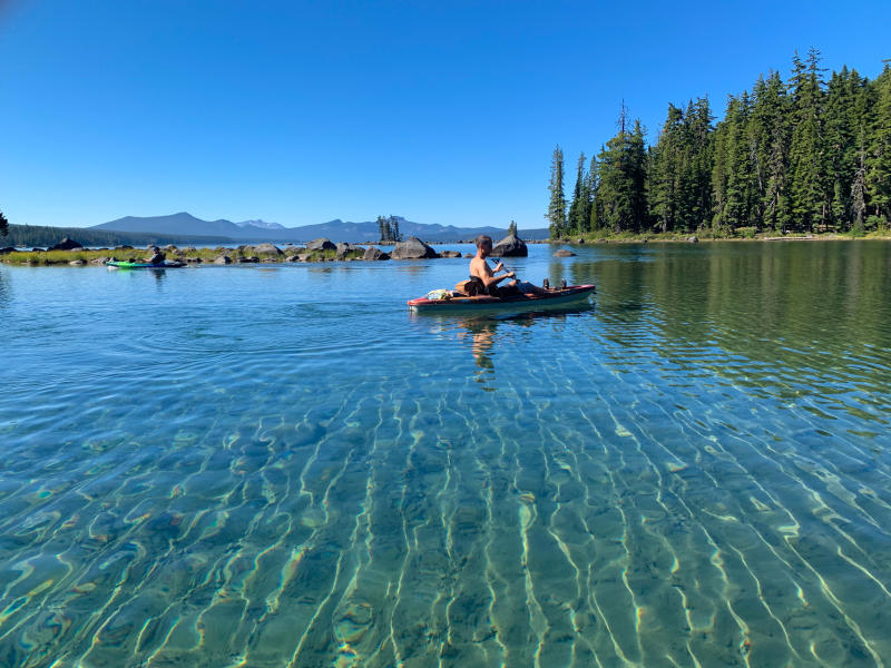 A kayaker on a clear blue cascade lake.
