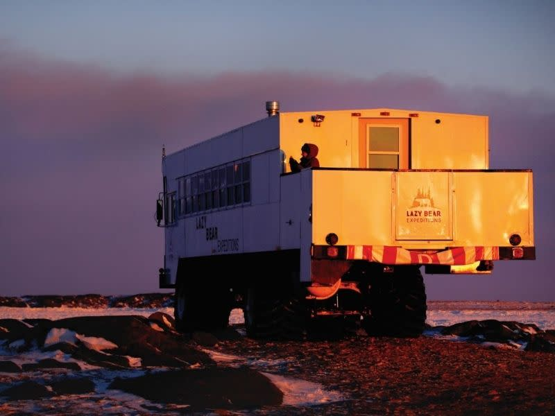 A Lazy Bear Expeditions tundra vehicle at sunset