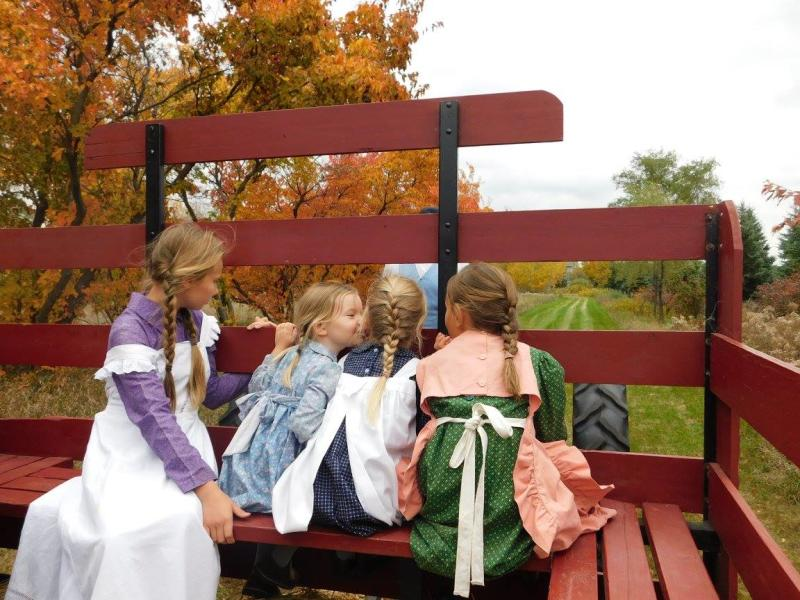 Four little girls dressed in early 1900s outfits ride in the back of a wagon during Fall on the Farm at Historic Eidem Farm