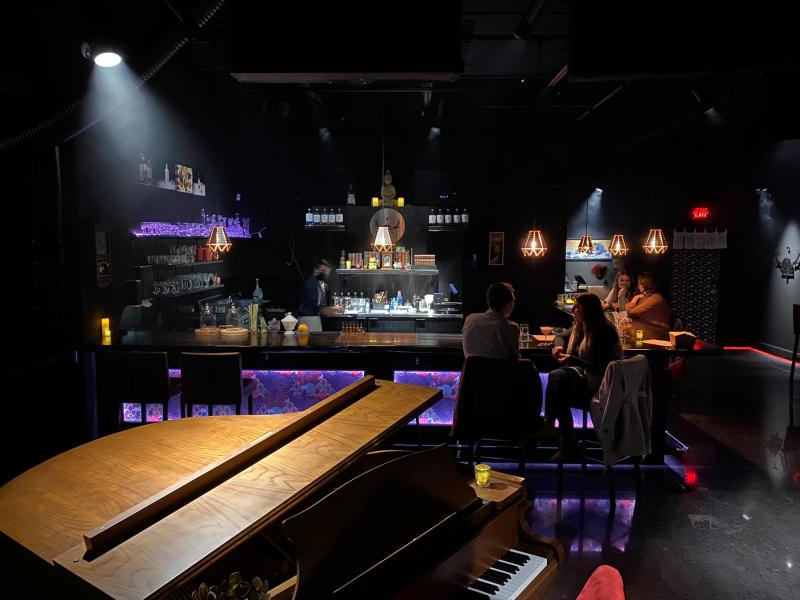 A couple dines along a bar with glowing purple lights at Skaalvenn Distillery cocktail lounge