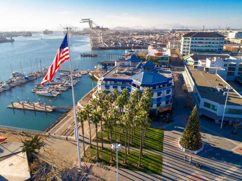 Aerial view of Jack London Square and with water and cranes in the background.