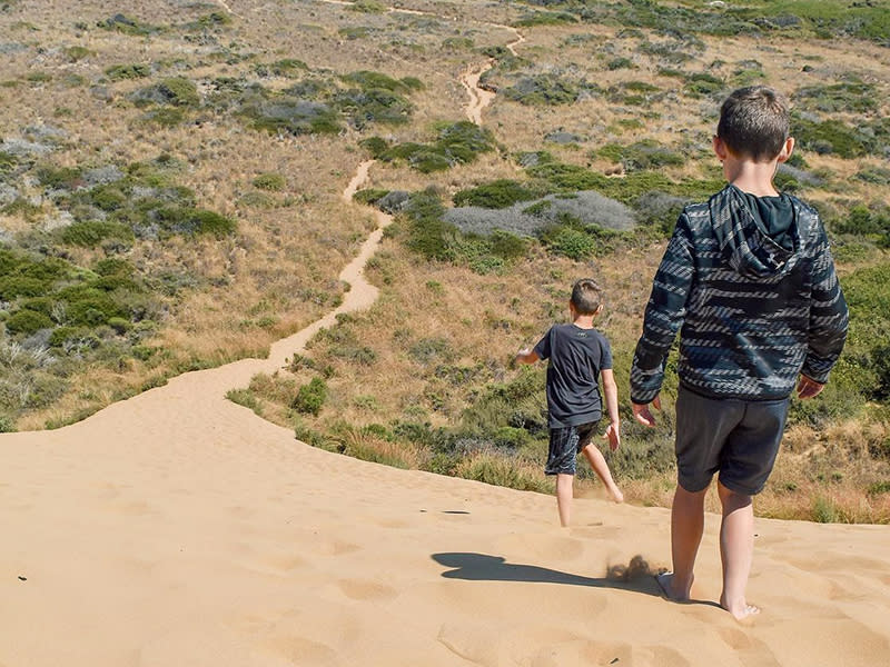 Two kids hiking down a sandy path at Harmony Headlands Park in SLO CAL