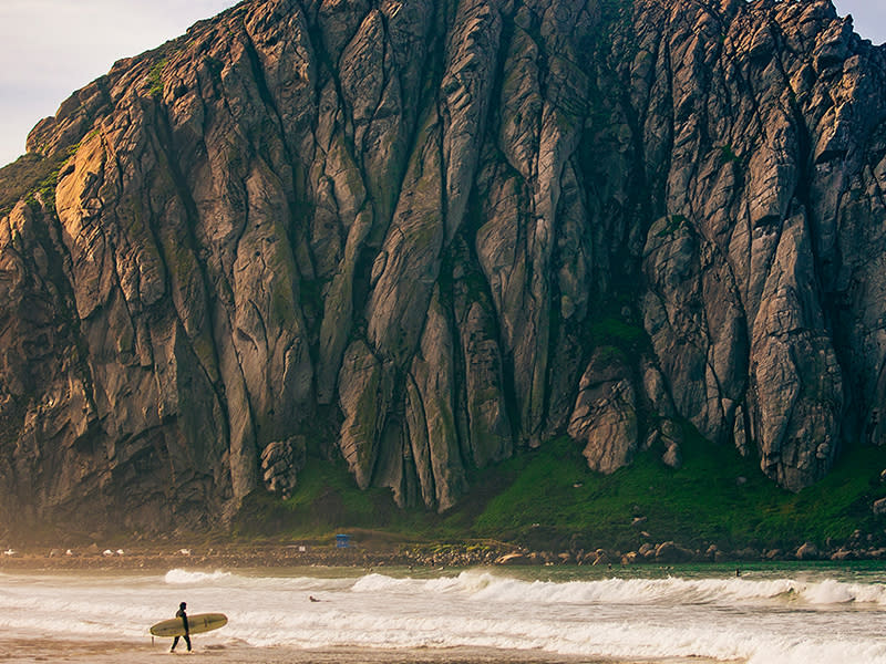 A surfer holding his board walks on the shore near Morro Rock