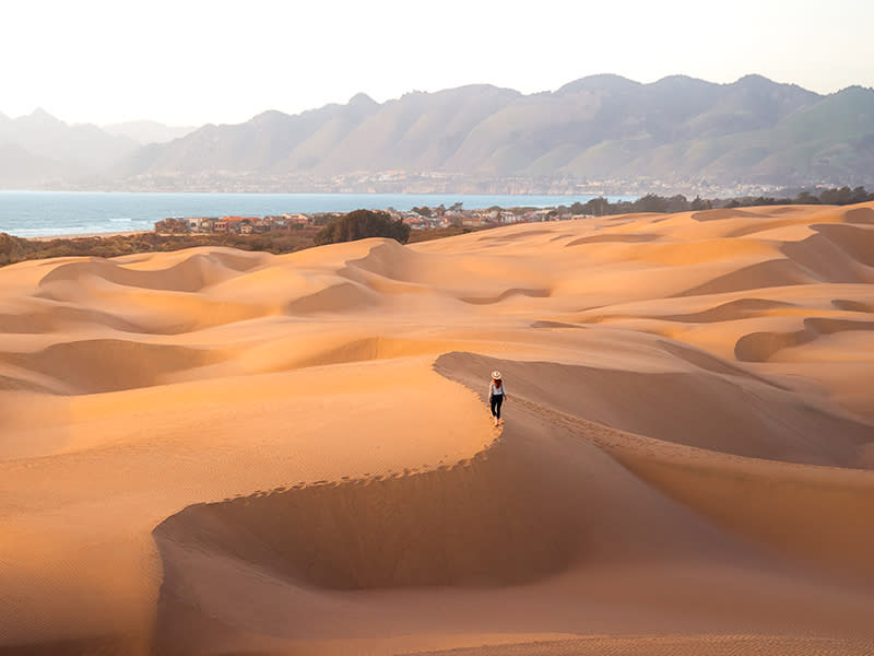 A person walking across the dunes at Oceano Dunes State Park in SLO CAL
