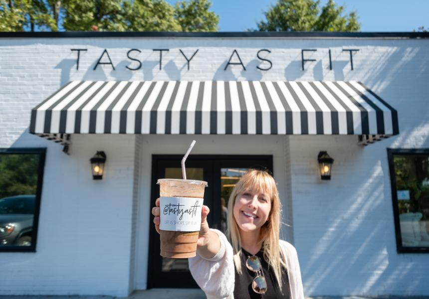 Woman holding out a smoothie in front of Tasty As Fit