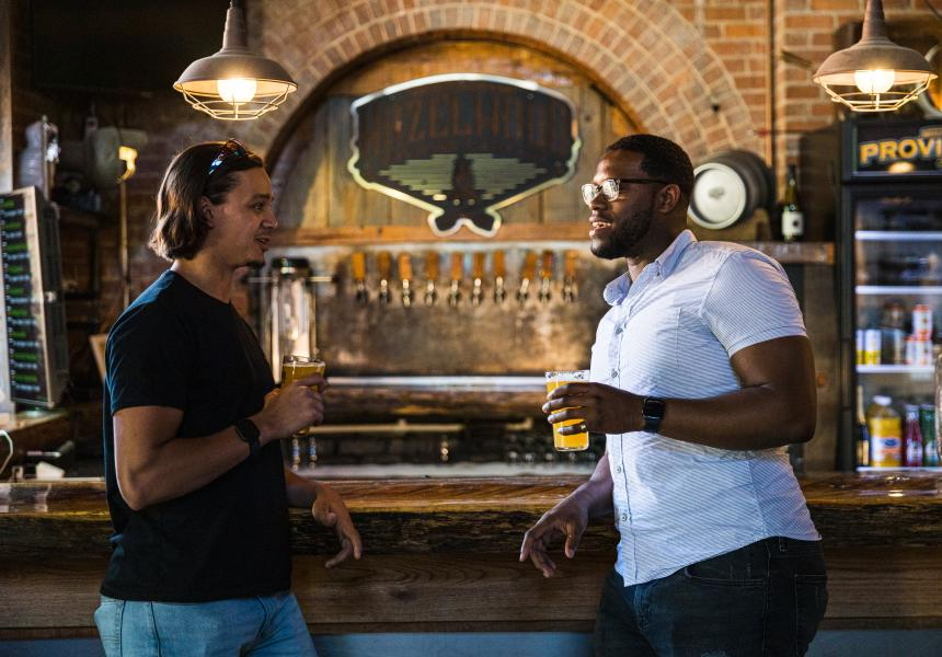 Two men drinking beer at a bar