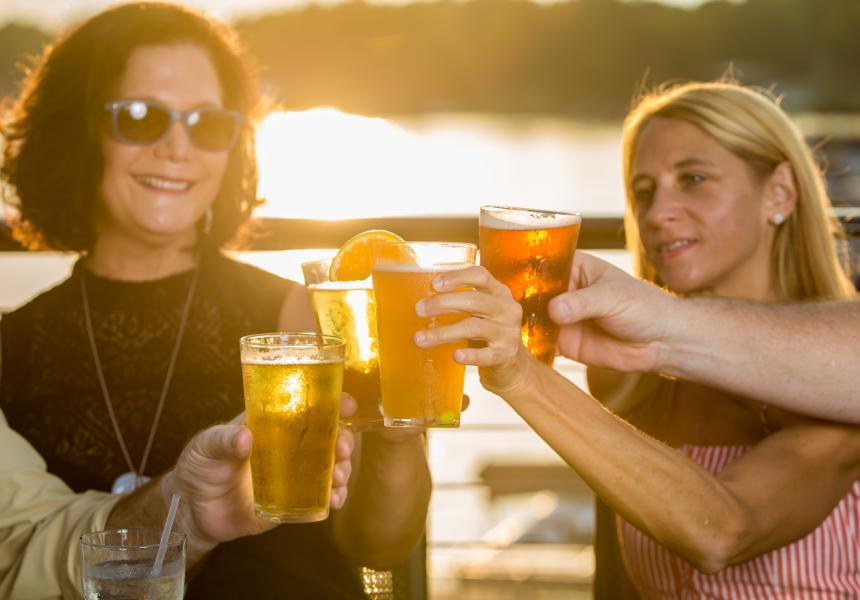 Friends cheers with beer at Liberty on the Lake