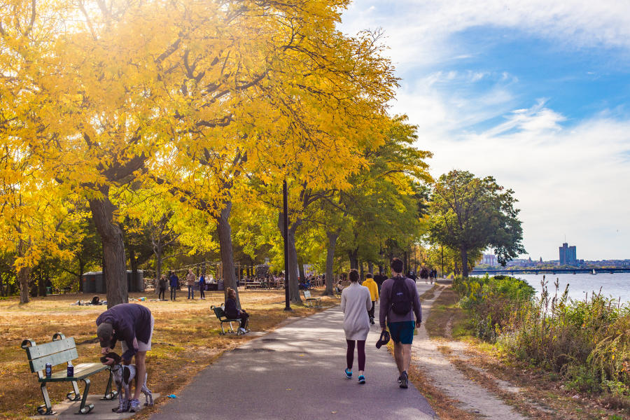 People sitting on benches and others walking on paved path along the Charles River Esplanade of Boston