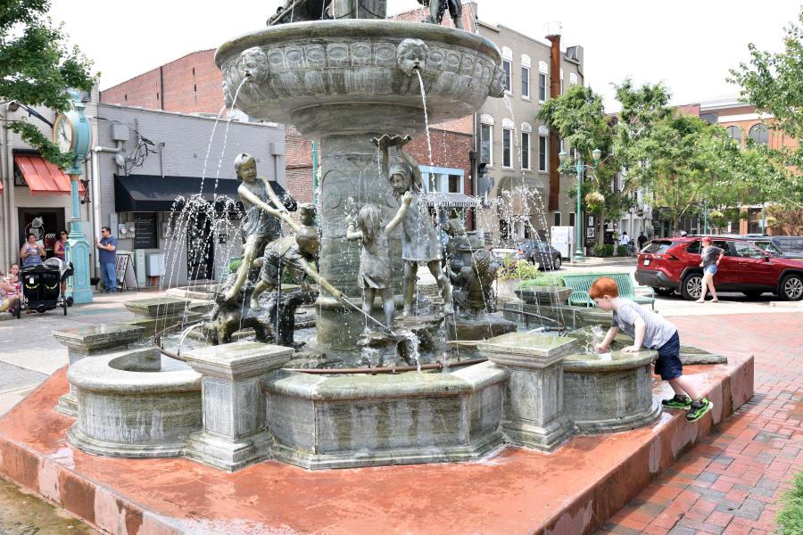 boy playing in fountain